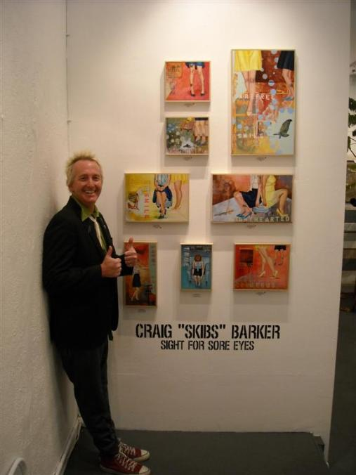 "Craig ""Skibs"" Barker alongside his wall of works"