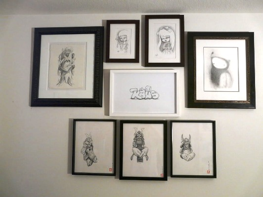 Wall of works on paper including pieces from Kaws, KuKula, Sam Flores, Tim Biskup, and Dan May
